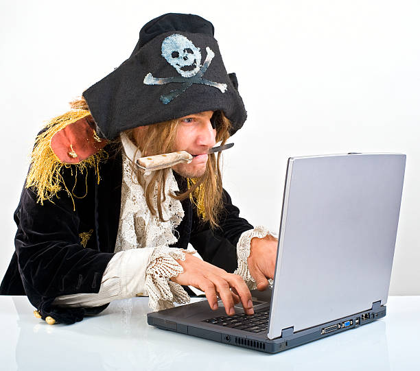 Man dressed as pirate with a knife in his mouth on a laptop pirate attacking with a knife a laptop computer  pirate criminal stock pictures, royalty-free photos & images