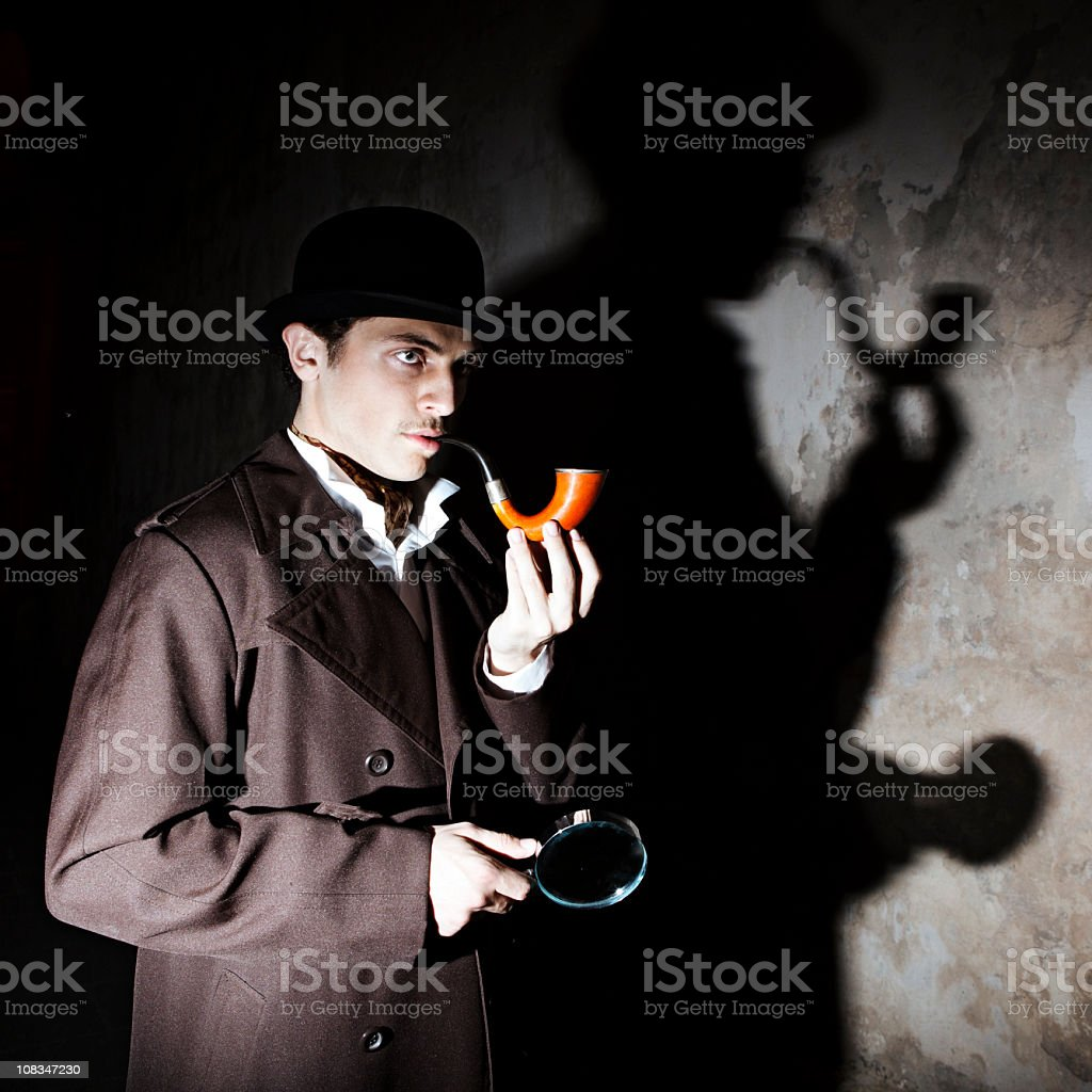 A man dressed as Sherlock Homes, with moody lighting stock photo