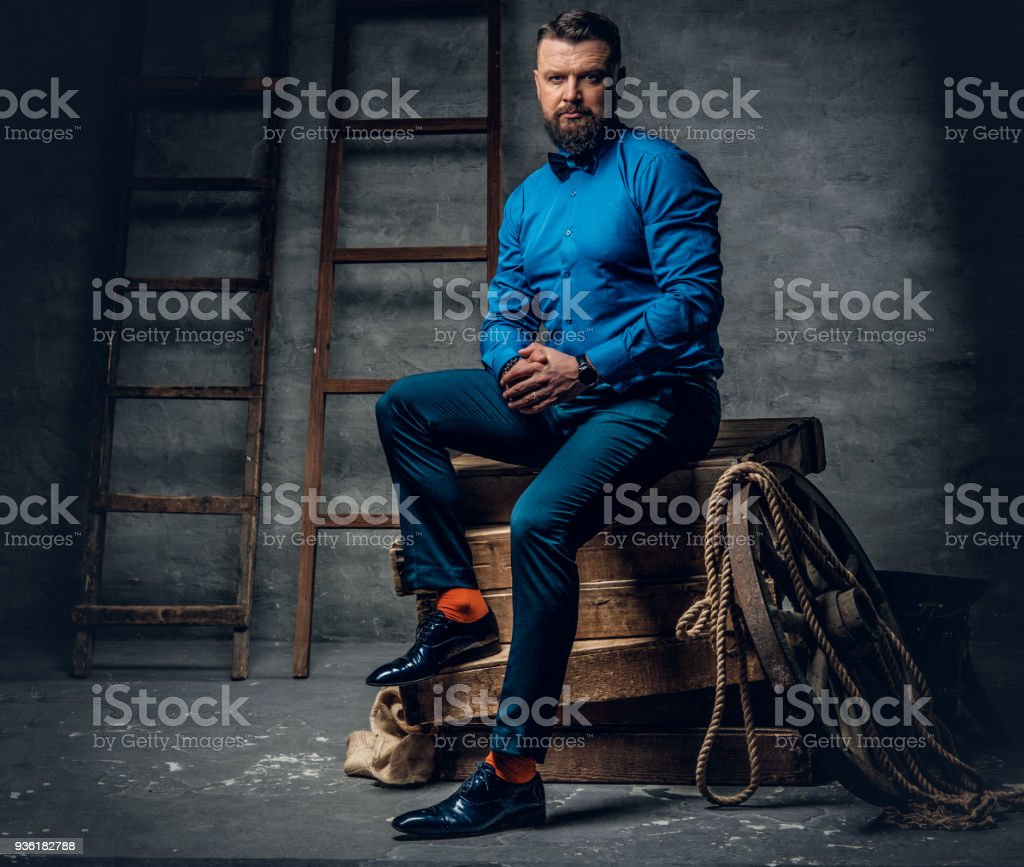A man dressed in a jeans, blue shirt and bow tie sits on a woode stock photo