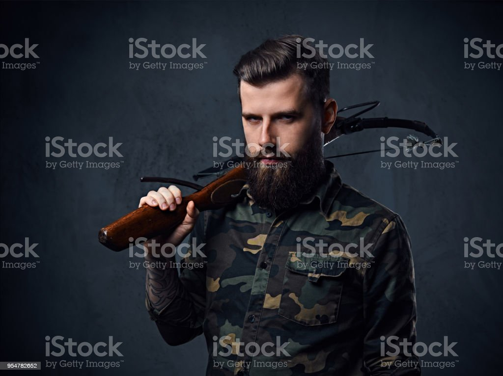 Un homme vêtu d'une veste militaire détient arbalète. - Photo