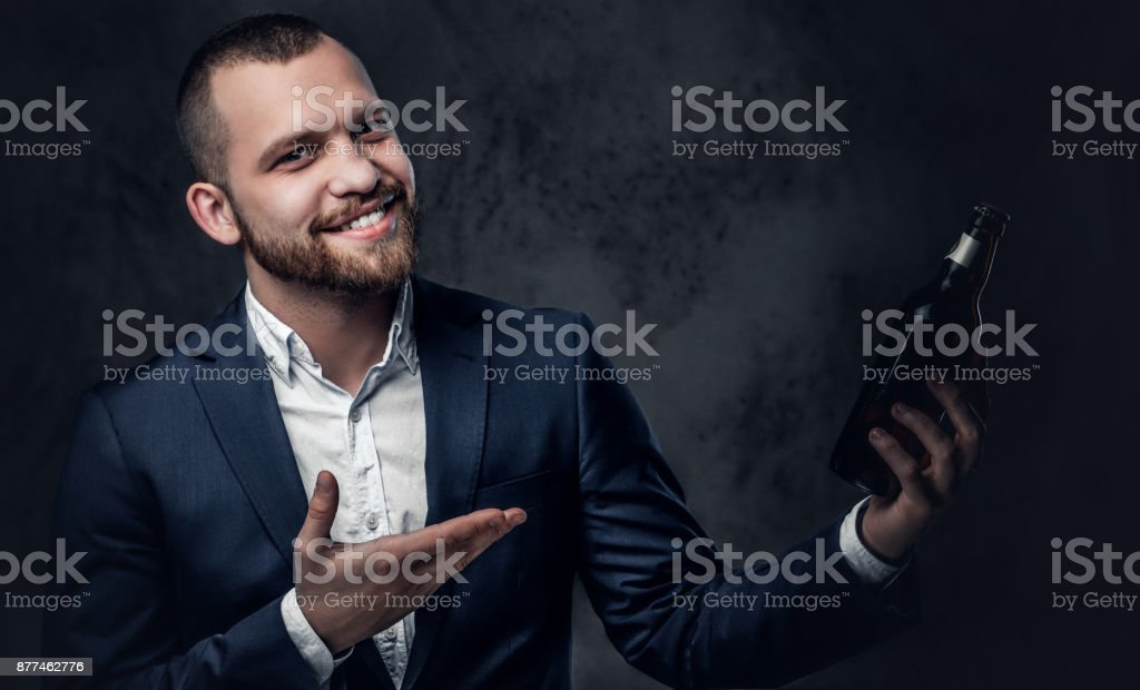 A trendy bearded male dressed in an elegant suit presenting craft...