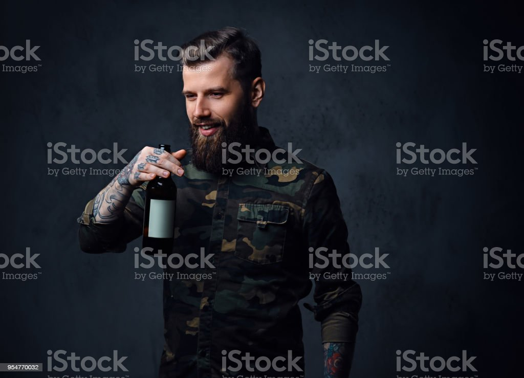 A tattooed, bearded hipster male dressed in military shirt, drinks...