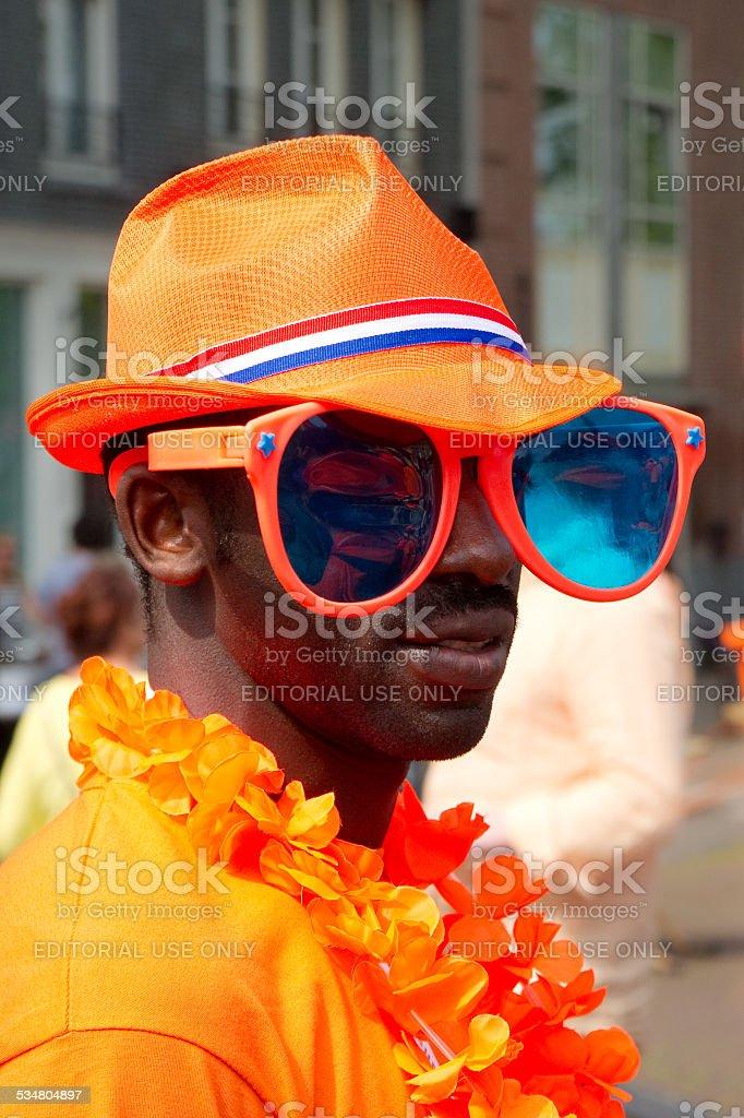 Man dressed in orange, wearing huge sunglasses stock photo