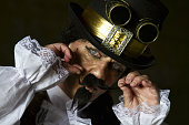 istock man dressed in steampunk, victorian clothing, dark wall background 478077546