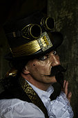 istock man dressed in steampunk, victorian clothing, dark wall background 478077578