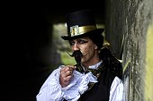 istock man dressed in steampunk, victorian clothing, dark wall background 478087188