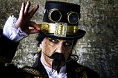 istock man dressed in steampunk, victorian clothing, dark wall background 478087194
