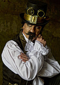 istock man dressed in steampunk, victorian clothing, dark wall background 478087196