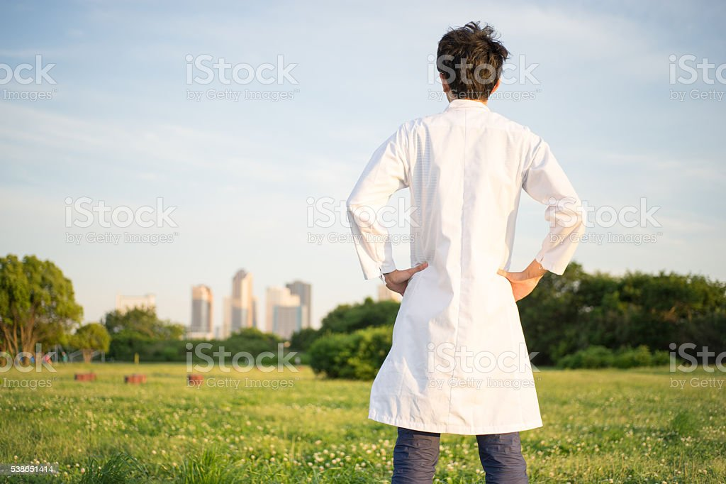 Man (building group, park, lawn) dressed in the white robe stock photo