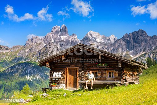 istock Man dressed in traditional Austrian or Bavarian clothes sitting on bench in front of alpine hut, enjoying beer in Alps 1252942869
