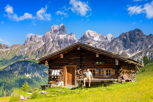 Young man sitting on bench in front of alpine hut, Sulzenalm, Salzburger Land