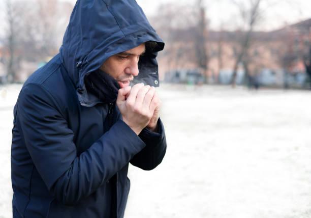 雪の降る天気で暖かい服装で服を着た男 ストックフォト