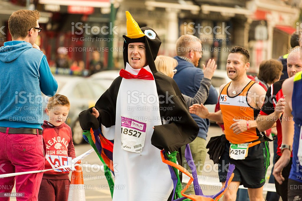 Man dressed like penguin in a race stock photo