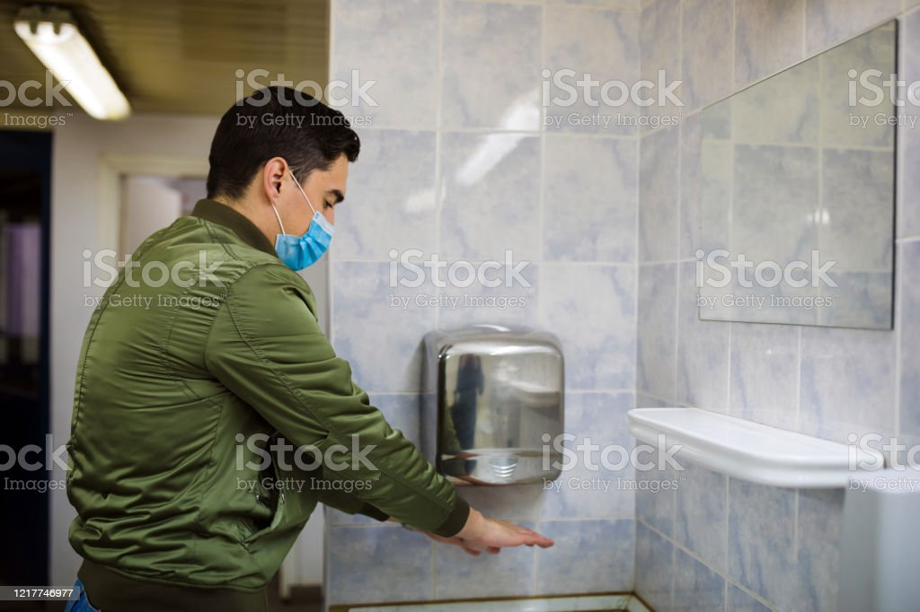 Man dries wet hands with an electric hand dryers Concept, diseases, viruses, allergies, air pollution. Portrait of a young man wearing a protective mask and washing his hands in a public bathroom. The face of a young man wearing a mask to prevent germs, toxic fumes and dust. Prevention of bacterial infection with Corone virus or Covid 19 in the air around streets and gardens. Above Stock Photo