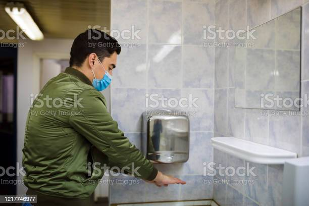 Man Dries Wet Hands With An Electric Hand Dryers Stock Photo - Download Image Now