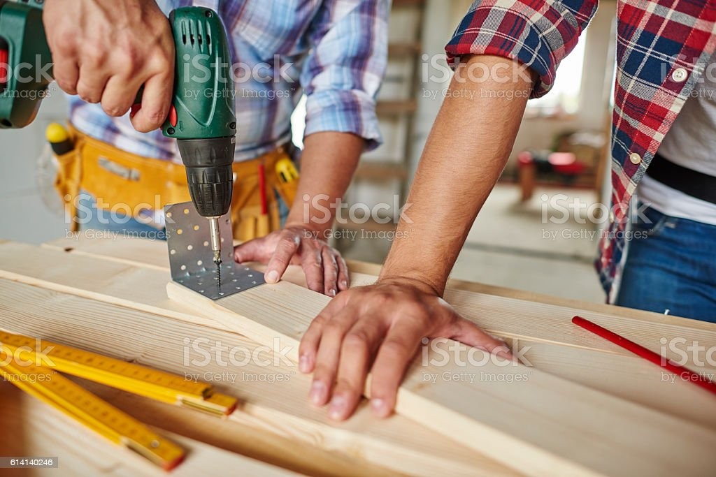 Man drilled a wooden plank and younger one helped stock photo