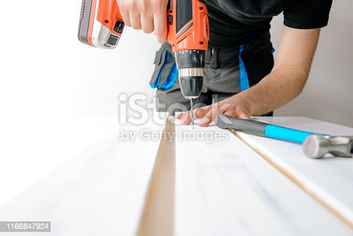 istock A man drilled by a drill in a wooden board. The concept of DIY and renovation of new things. 1166847924