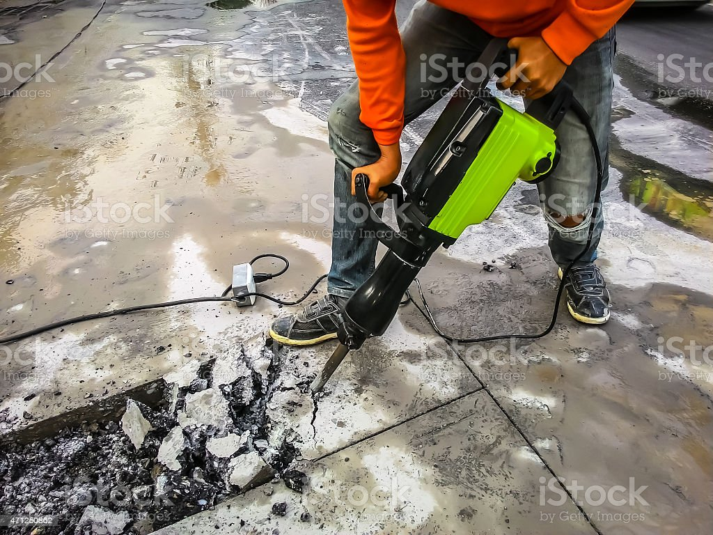 Man drilling road stock photo