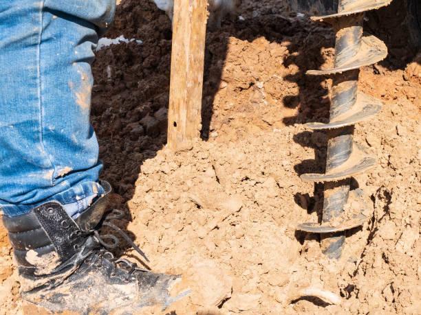człowiek wierci studnię geologiczną. zbliżenie buta, śruby i gleby - geologia zdjęcia i obrazy z banku zdjęć
