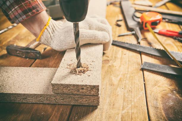 Man drills the wooden plank stock photo