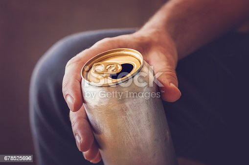 istock Man drinking a cold beer after work in the evening. Hand holding a aluminum can. 678525696