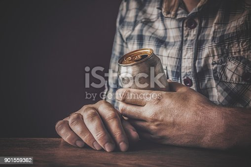 istock Man drinking a cold beer after work in the evening. Hand holding a aluminum can. Resting time in the bar or pub. Dark depressive atmosphere. Alcohol problem concept. 901559362