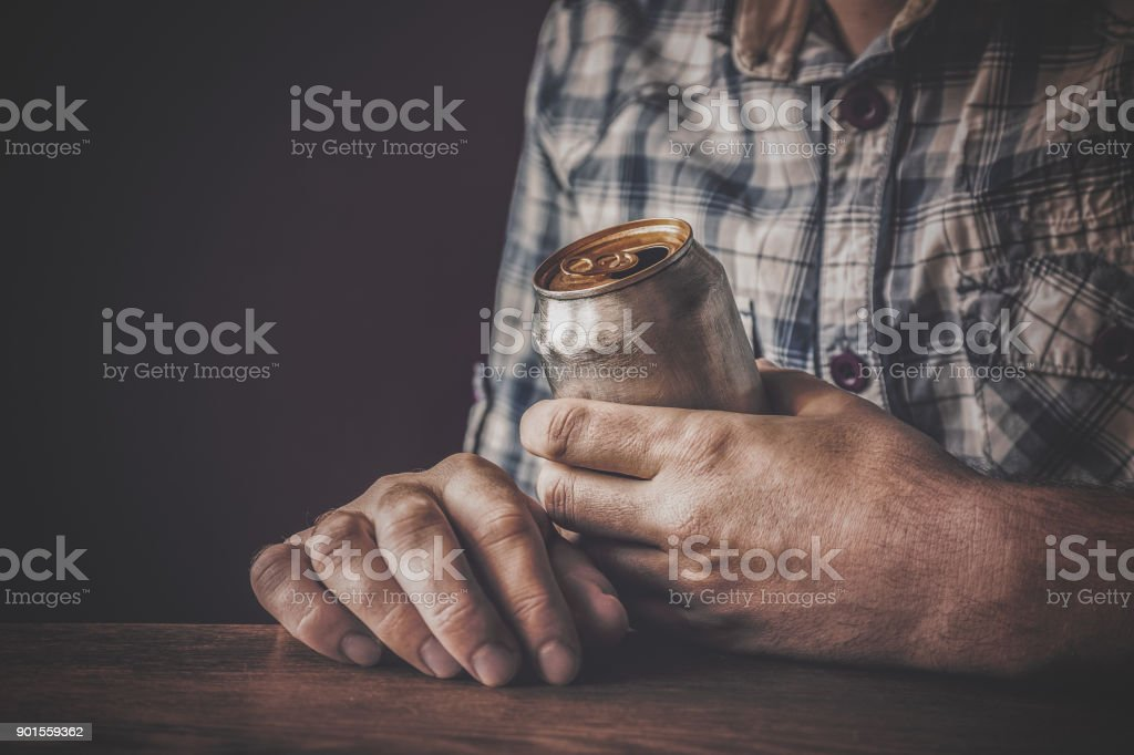 Man drinking a cold beer after work in the evening. Hand holding a aluminum can. Resting time in the bar or pub. Dark depressive atmosphere. Alcohol problem concept. stock photo