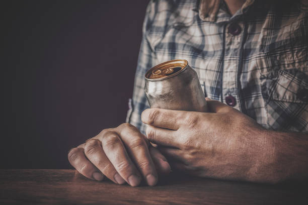 man drinking a cold beer after work in the evening. hand holding a aluminum can. resting time in the bar or pub. dark depressive atmosphere. alcohol problem concept. - dipsomania stock pictures, royalty-free photos & images