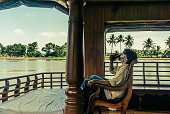 Man drinking aboard a Houseboat on the Kerala Backwaters in South of India.