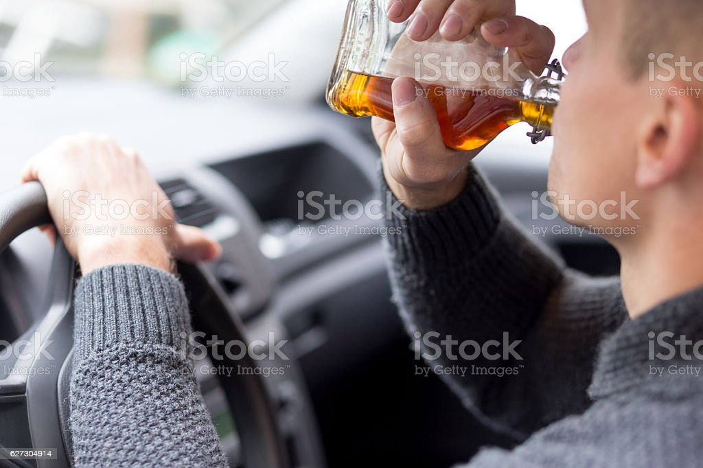 Man drinking alcohol and driving stock photo