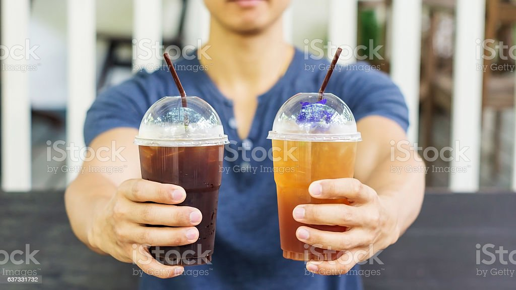Man drinking an iced coffee and iced tea. stock photo