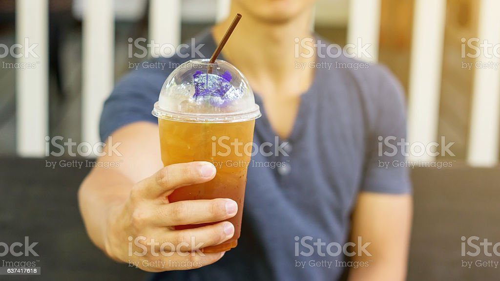 Man drinking an iced fruit tea in a cafe. stock photo