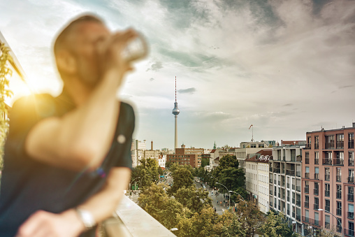 man drinking at balcony with view on Berlin skyline