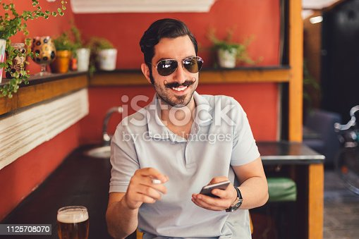Young man at cafe texting on phone