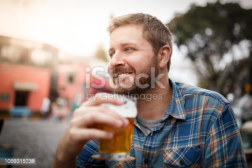 Blonde man drinking beer at the bar