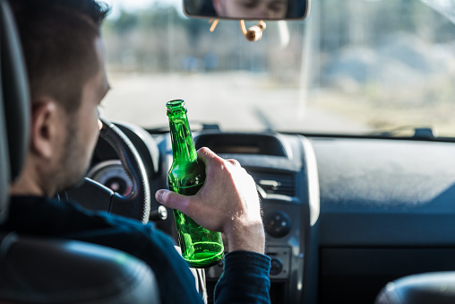 istock Man drinking beer while driving a car 1020544662