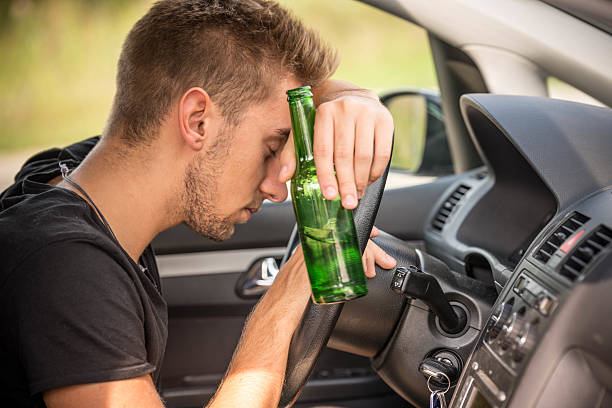 Man drinking beer while driving a car stock photo