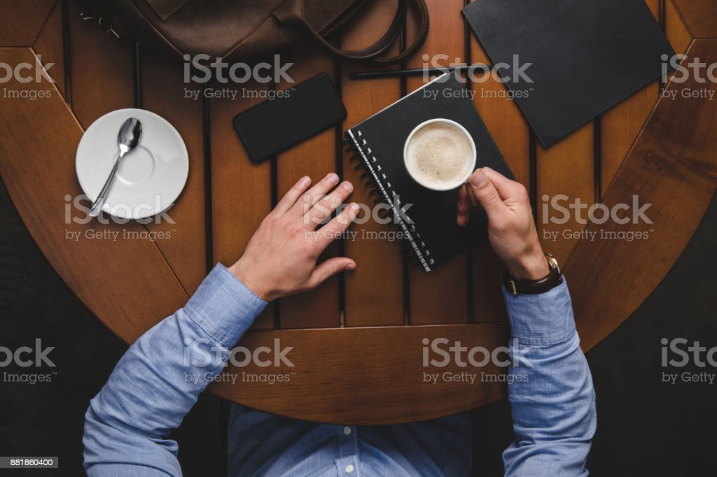 man drinking coffee at table stock photo