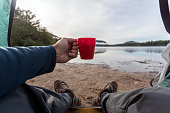 A man is drinking a coffee by the lake in camping. He is sitting in his tent and contemplating the view. You can see his personal perspective of the nature surrounding him.
