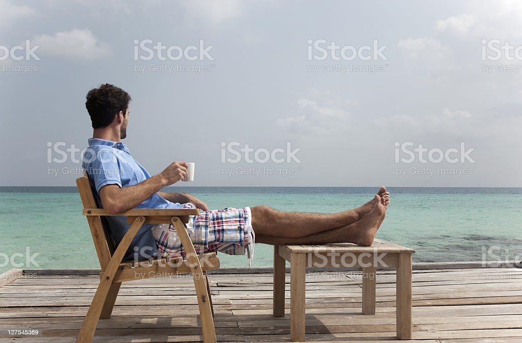 Man drinking coffee on deck at beach stock photo