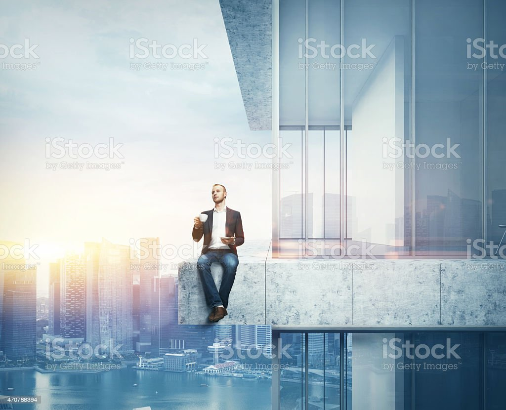 Man drinking coffee on the border of the skyscraper stock photo