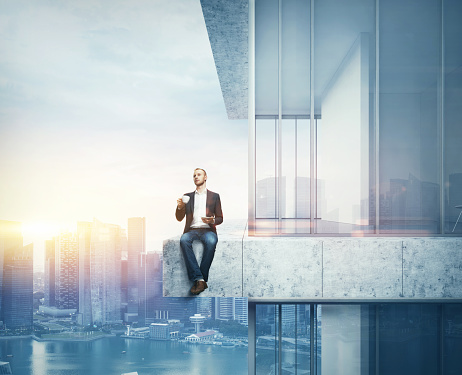 Man Drinking Coffee On The Border Of The Skyscraper Stock Photo - Download Image Now