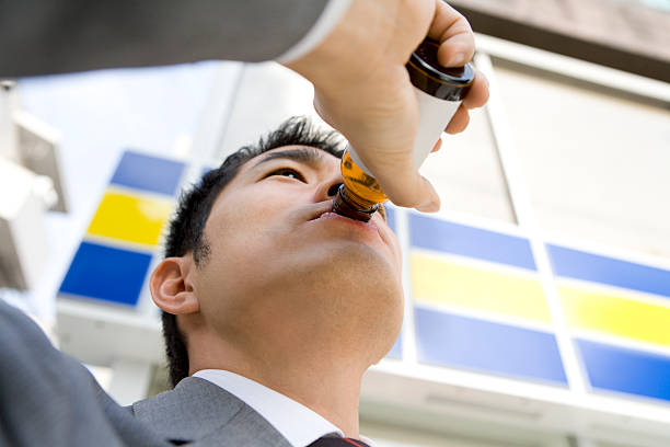Man drinking energy drink in front of convenience store stock photo