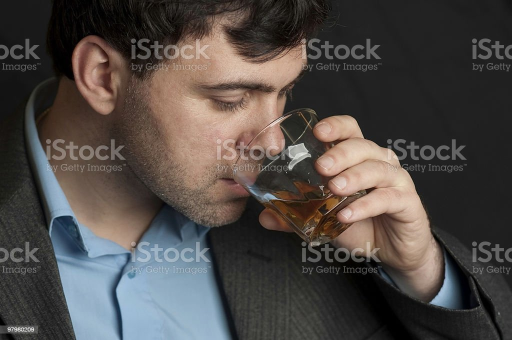 Man drinking from a glass of whiskey royalty-free stock photo