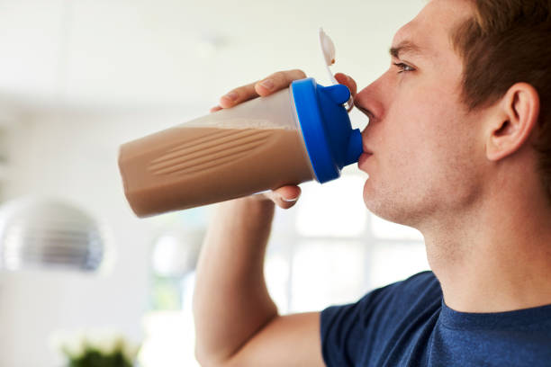 man drinking protein shake in kitchen at home - protein stock photos and pictures