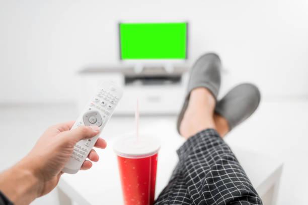 Mann trinkt Sodasaft und schaut auf TV mit Beinen auf dem Tisch im Wohnzimmer. Chroma-Taste grüner Bildschirm. – Foto