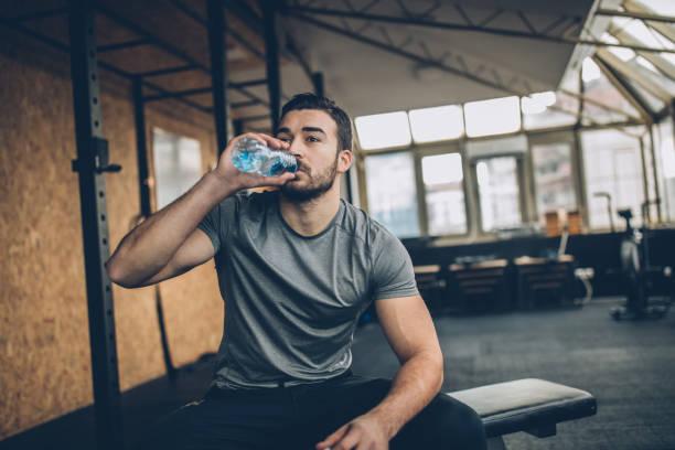 mann trinkwasser nach dem training im fitness-studio - wasser trinken abnehmen stock-fotos und bilder