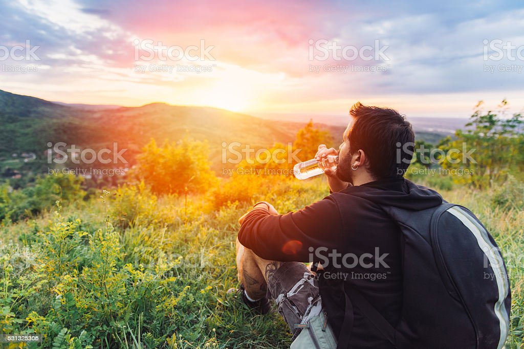 Man drinking water and enjoying mountain sunset