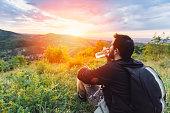 Man drinking water and enjoying mountain sunset