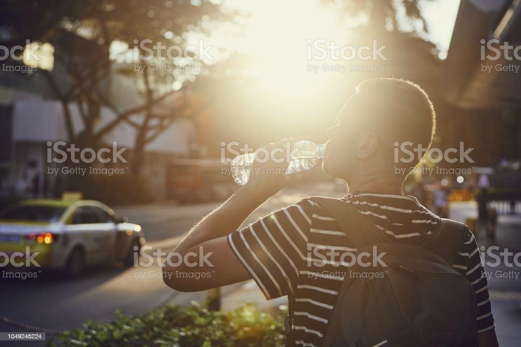 Man drinking water at sunset stock photo